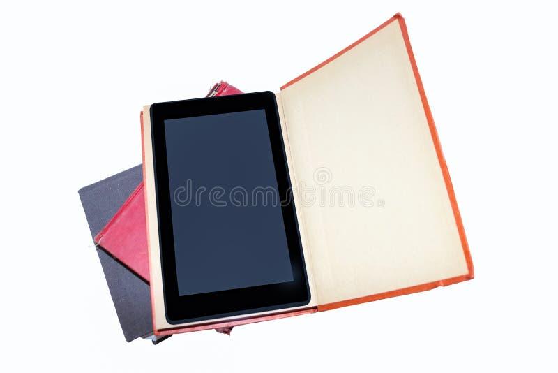 -在一本旧书里面的片剂在堆旧书-被隔绝的E读者-文本的室 图库摄影