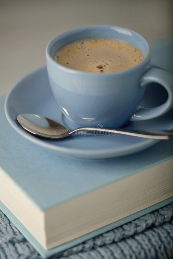 在一本浅兰的杯子和书的咖啡在与knitt的蓝色捆绑 库存照片