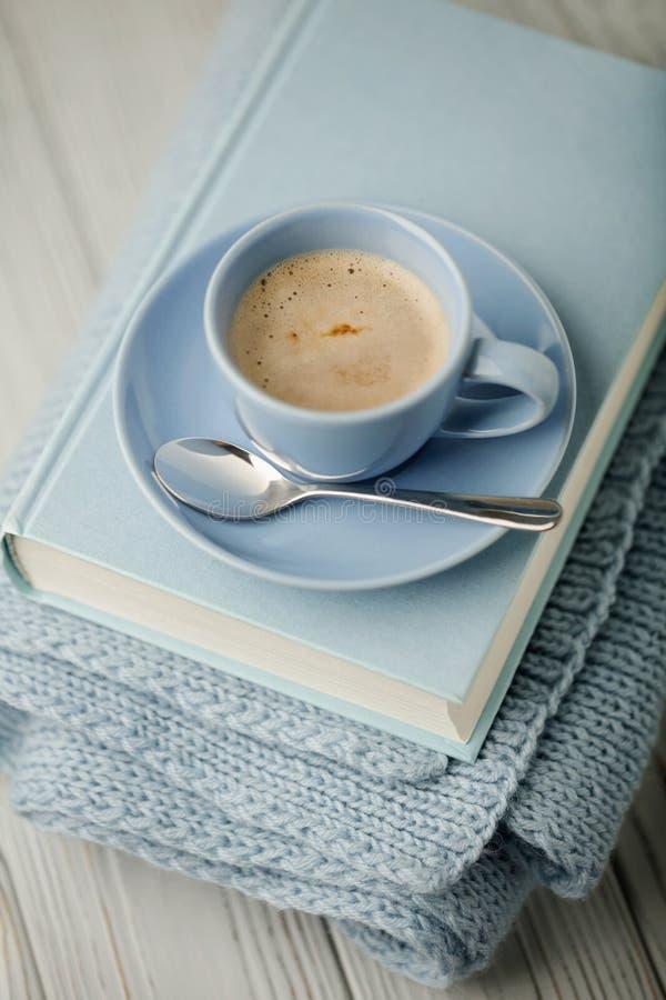 在一本浅兰的杯子和书的咖啡在与knitt的蓝色捆绑 图库摄影