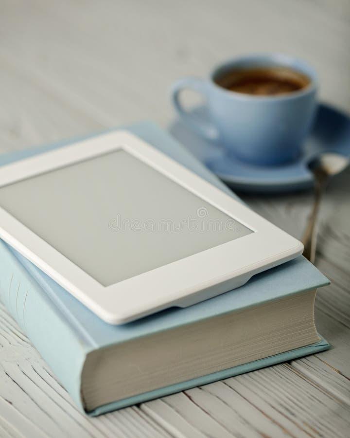 在一本浅兰的杯子和书的咖啡在有选出的蓝色盖子 库存照片