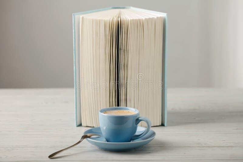 在一本浅兰的杯子和书的咖啡在木ba的蓝色盖子 库存照片