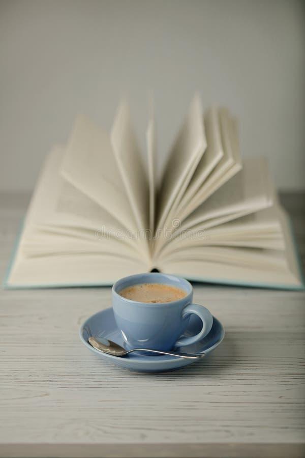 在一本浅兰的杯子和书的咖啡在木ba的蓝色盖子 库存图片