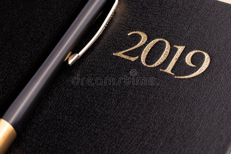 在一本闭合的黑笔记本日志的一支笔与题字2019年 库存照片