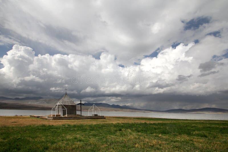 在一朵巨大的白色云彩下的小教会在Foka村庄  免版税图库摄影
