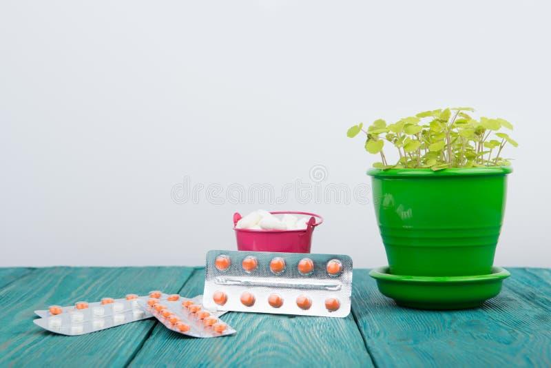 在一朵桃红色桶和花的许多不同的药片在蓝色木头de 库存图片