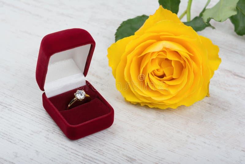 在一朵红色礼物盒和黄色玫瑰的金黄珍珠圆环在白色木背景 免版税库存图片