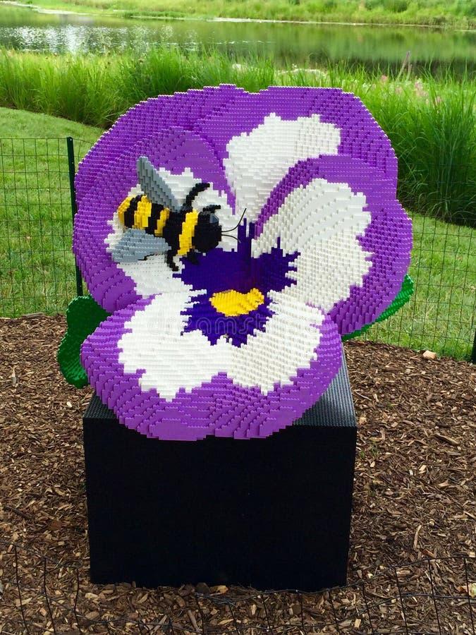 在一朵蝴蝶花的蜂在乐高中 免版税库存图片