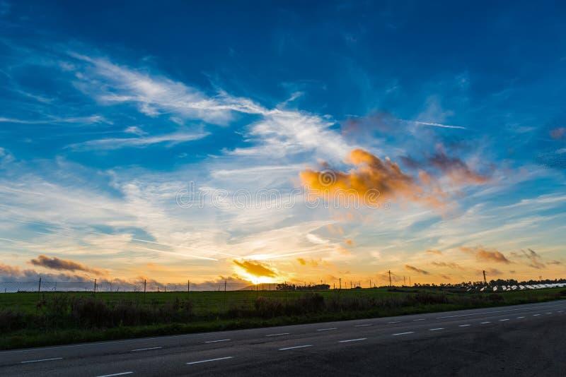 在一条乡下公路的五颜六色的天空在日落 免版税图库摄影