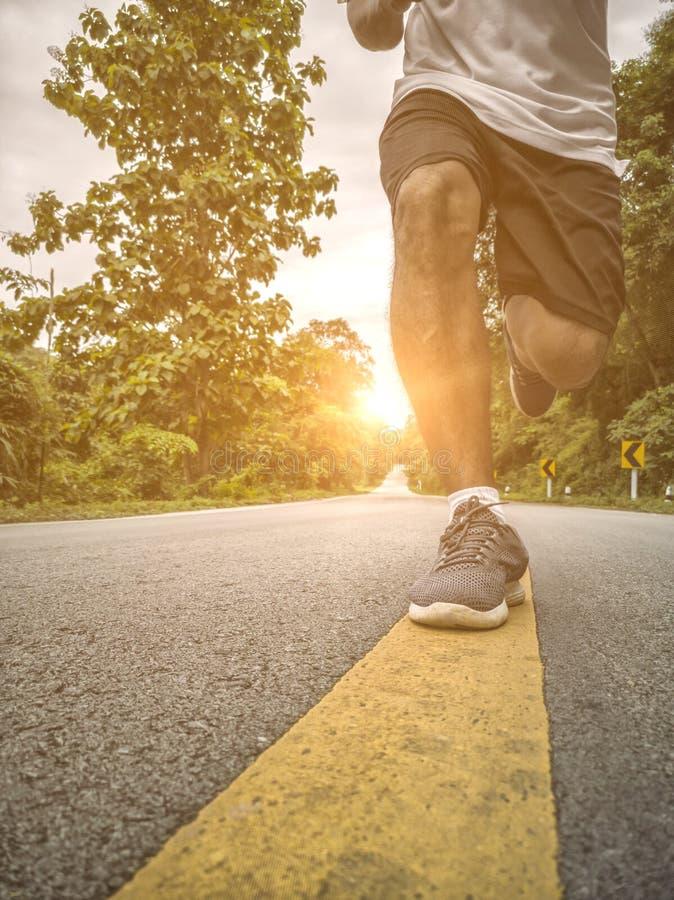 在一条农村路的年轻男性赛跑在日落期间 库存图片