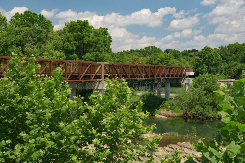 在一条地方林荫道路的一个人行桥 免版税库存图片