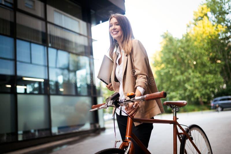 在一条城市街道上的年轻女实业家身分有自行车的 图库摄影