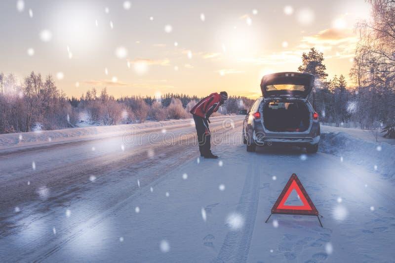 在一条多雪的冬天路的残破的汽车 库存图片