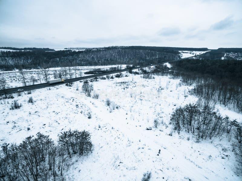 在一条多雪的领域和路的鸟瞰图从quadrocopter 库存图片