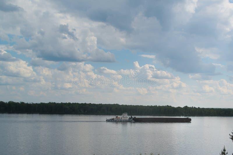 在一条宽河的货船航行 免版税库存照片