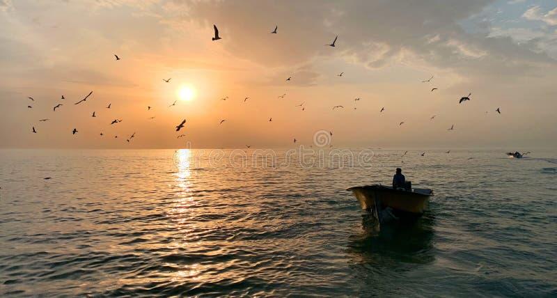 在一条小划艇的男性在有发光在背景中的太阳的美丽的海中间 免版税库存照片