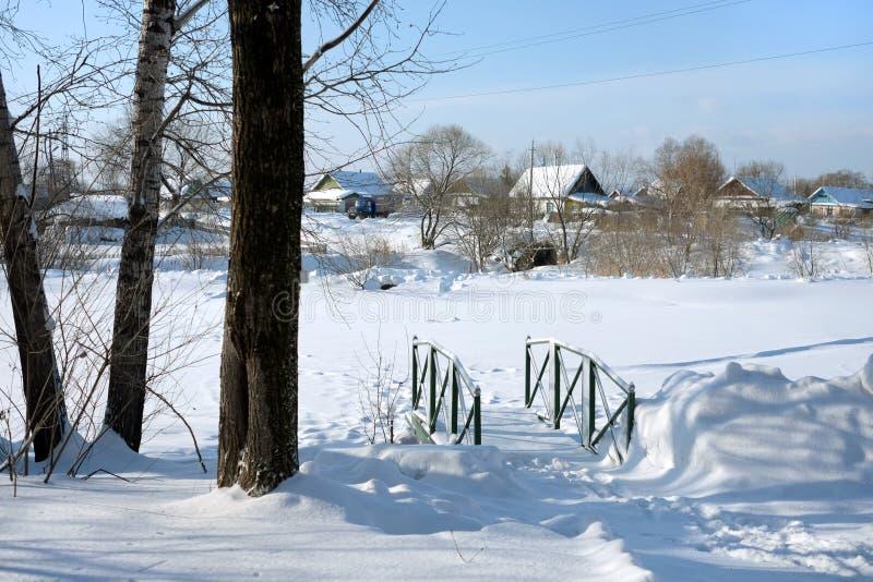 在一条小小河的一座桥梁,冬天在村庄,在雪下的地面 免版税图库摄影