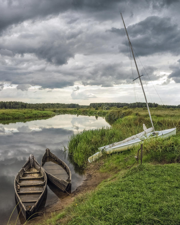 在一条小河的河岸的老小船 图库摄影