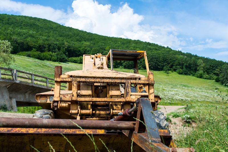 在一条小河附近的被放弃的,老微型挖掘机 免版税库存照片