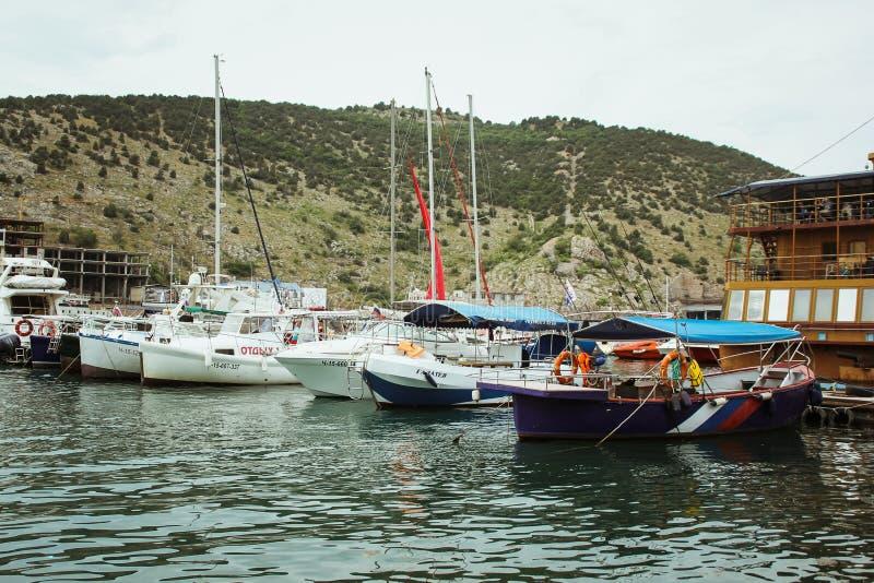 在一条小船的休闲在一座美丽的山的岸 游艇和小船在Balaklava美丽的海湾  美丽如画的钓鱼 图库摄影