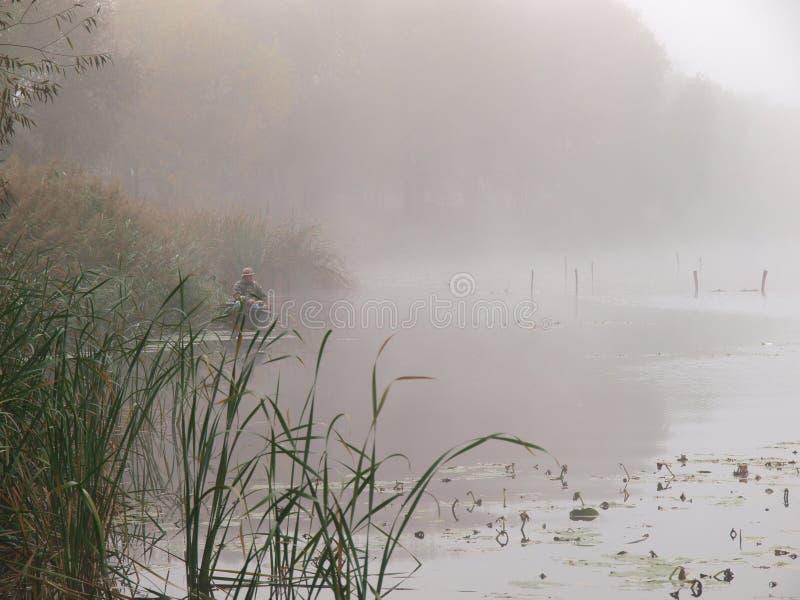 在一条小船的渔夫剪影在一个有薄雾的早晨湖 库存照片