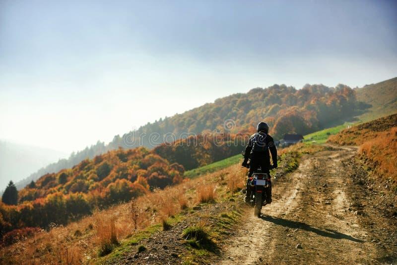 在一条山土路的摩托车在秋天 库存照片