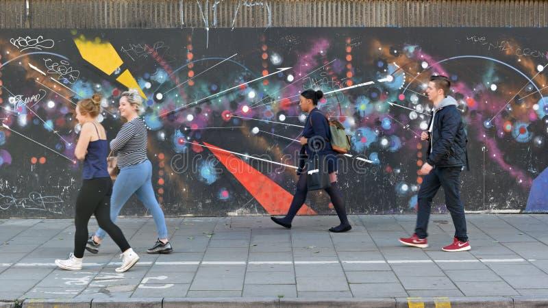 在一条拥挤的街上的街道画墙壁 库存图片