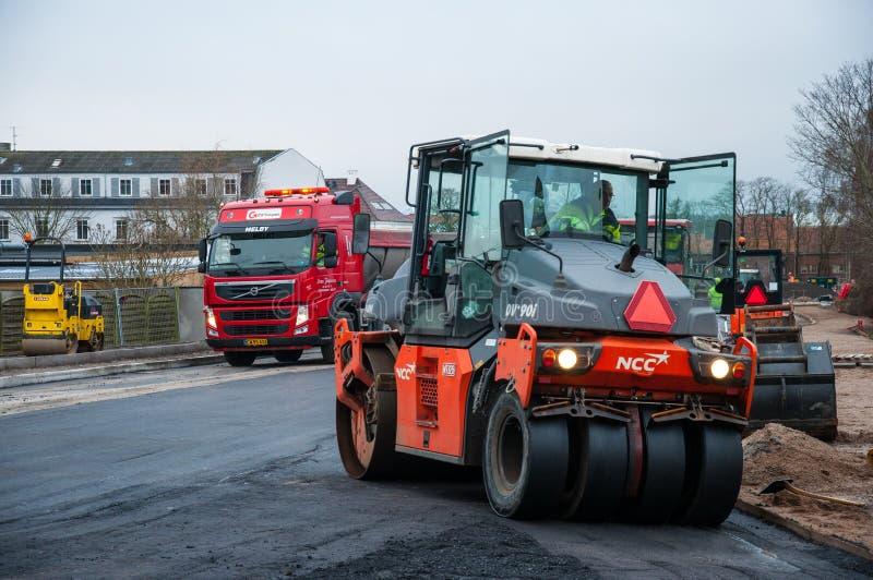 在一条新的路的压路机变紧密的柏油碎石地面沥青在丹麦 免版税库存照片