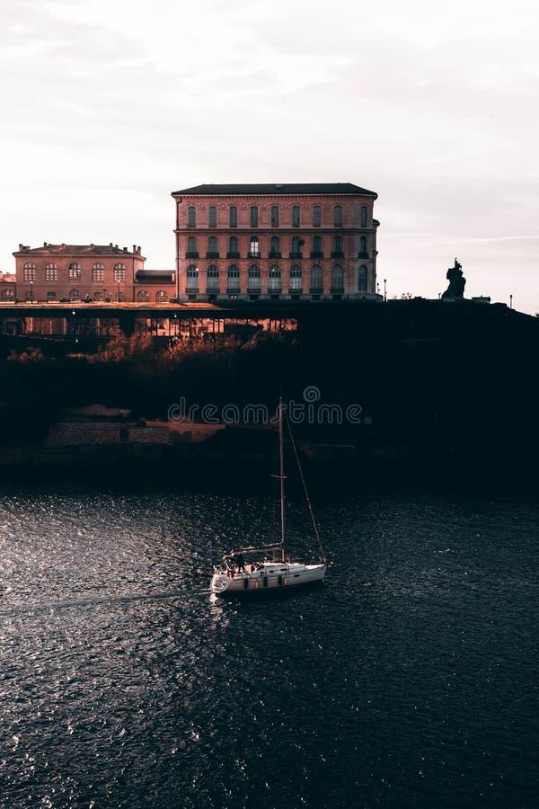 在一条河的小船航行在马赛,有令人惊讶的建筑学的法国在背景中 免版税库存照片
