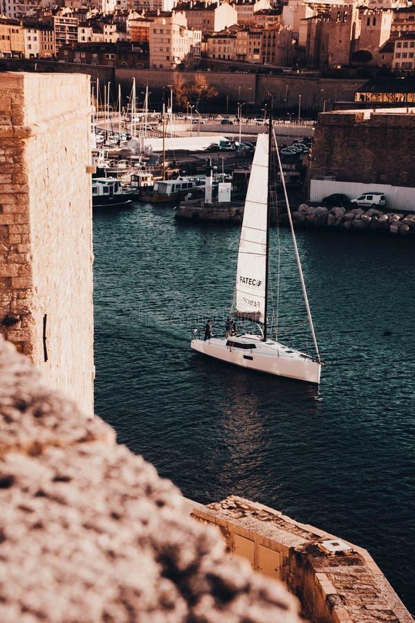 在一条河的小船航行在马赛,有令人惊讶的建筑学的法国在背景中 库存照片