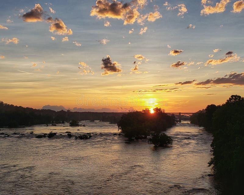 在一条河的美好的金黄日落有铁路桥梁的 免版税库存照片