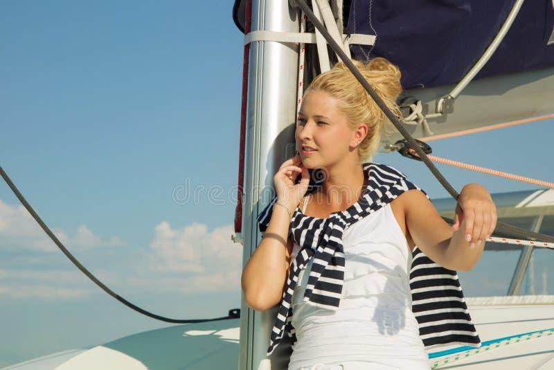 在一条游艇的有吸引力的女孩航行在夏日 免版税库存图片