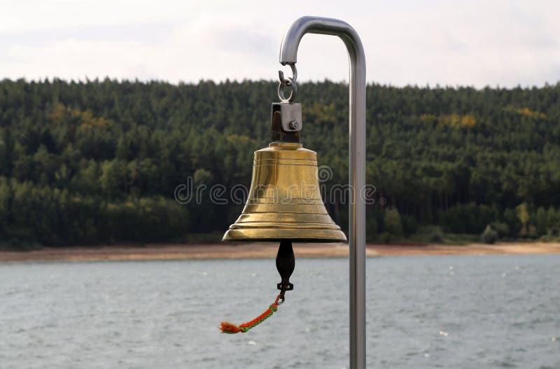 在一条游艇的铜响铃在海岸线的背景 免版税库存照片