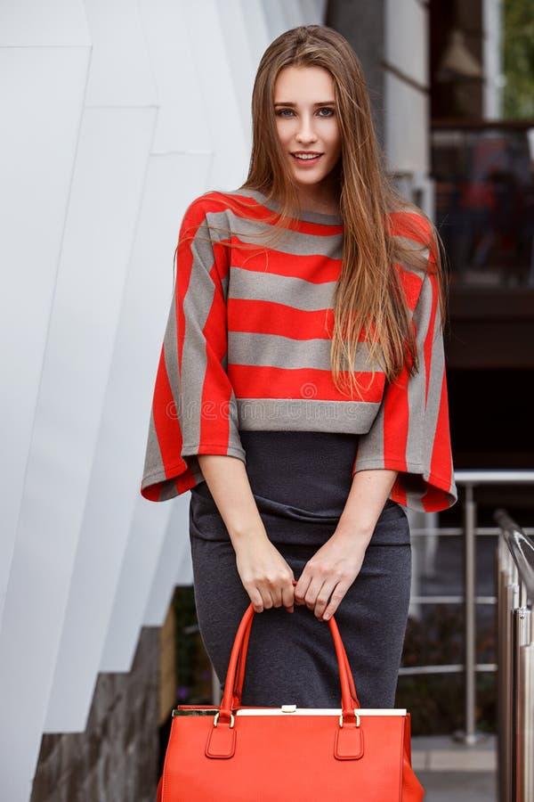 在一条灰色裙子,一件镶边红色和灰色女衬衫打扮的时兴的女孩拿着一个红色袋子在街道摆在 库存照片