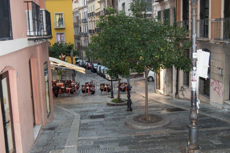 在一条狭窄的被修补的街道上的传统室外咖啡馆在雨以后在卡利亚里,意大利,2018年10月09日,选择聚焦 免版税库存照片