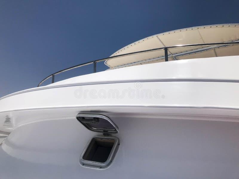 在一条白色大巡航游艇,船,小船,反对蓝天的巡航划线员的一个小观察孔 免版税图库摄影