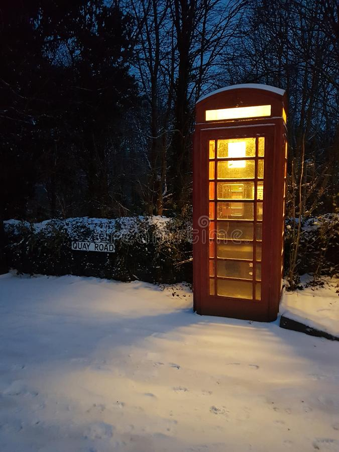 在一条积雪的村庄街道上的电话亭 免版税库存图片