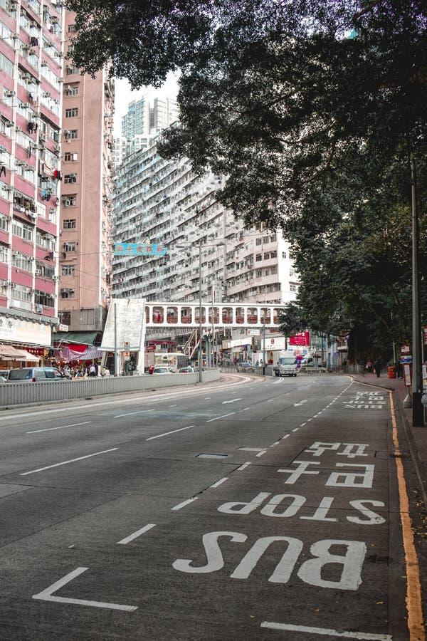 在一条空的街道上的公交车站在有大居民住房的香港在背景中 免版税库存图片
