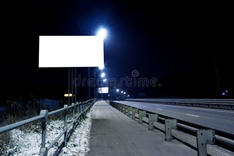 在一条空的路的晚上,高速公路里倒空空白的广告牌 库存照片