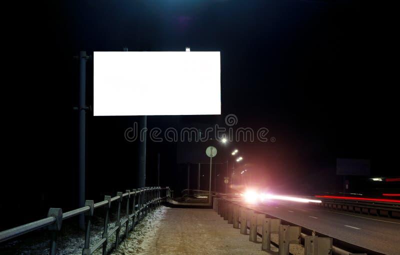 在一条空的路的晚上,高速公路里倒空空白的广告牌 免版税库存图片