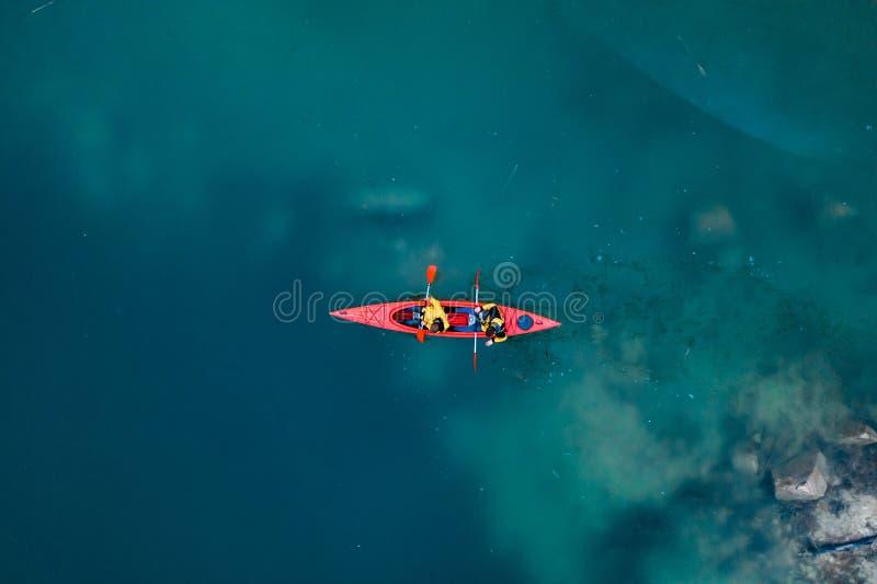 在一条红色小船的两个运动人浮游物在河 免版税图库摄影