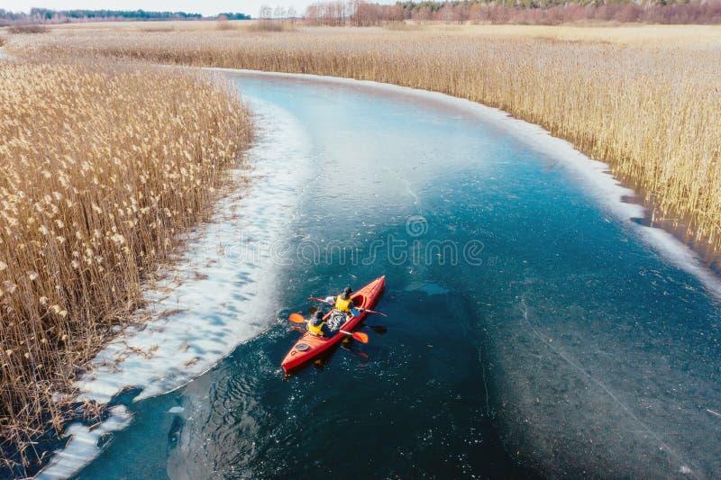 在一条红色小船的两个运动人浮游物在河 库存图片