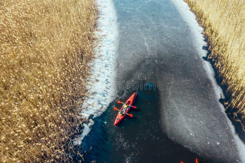 在一条红色小船的两个运动人浮游物在河 库存照片