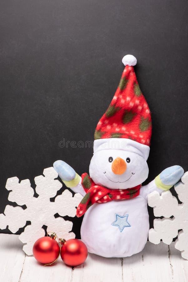 在一条红色帽子和围巾的快乐的雪人玩具有在黑粉笔板背景的泡沫雪花的  库存图片