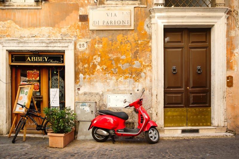 在一条老狭窄的铺有鹅卵石的街道上的红色滑行车在罗马 库存照片