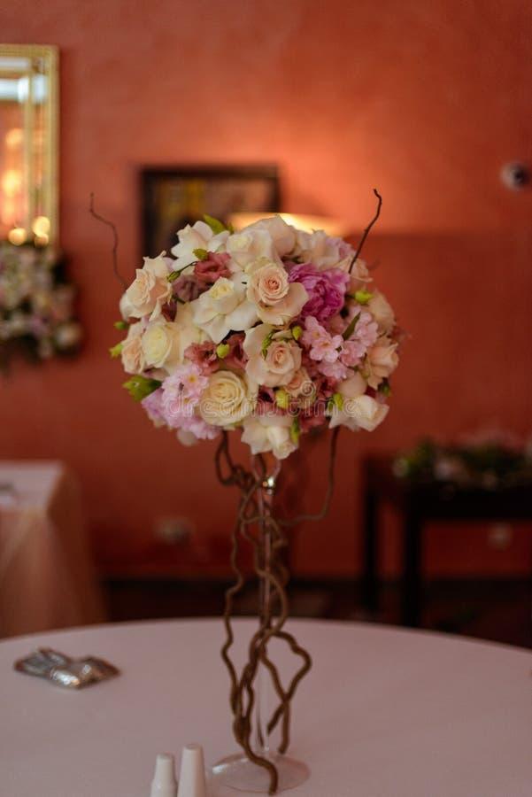 在一条腿的玫瑰花束在庆祝商店floristry或婚姻的沙龙的餐馆内部 免版税库存图片