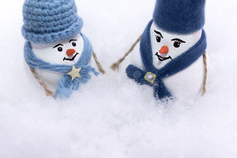 在一条蓝色帽子和围巾的两个雪人在雪随风飘飞的雪站立  免版税库存图片