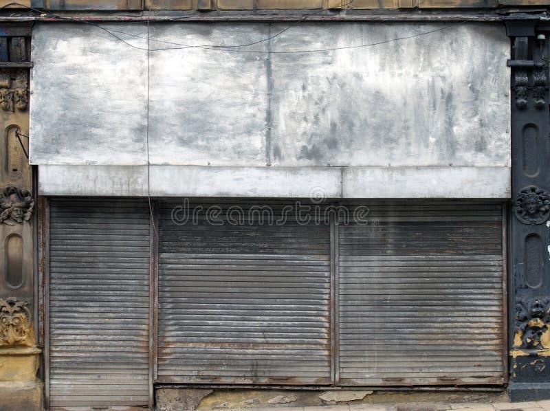 在一条街道上的一家被放弃的商店有在商店前面和门的闭合的肮脏的生锈的金属快门的 免版税图库摄影