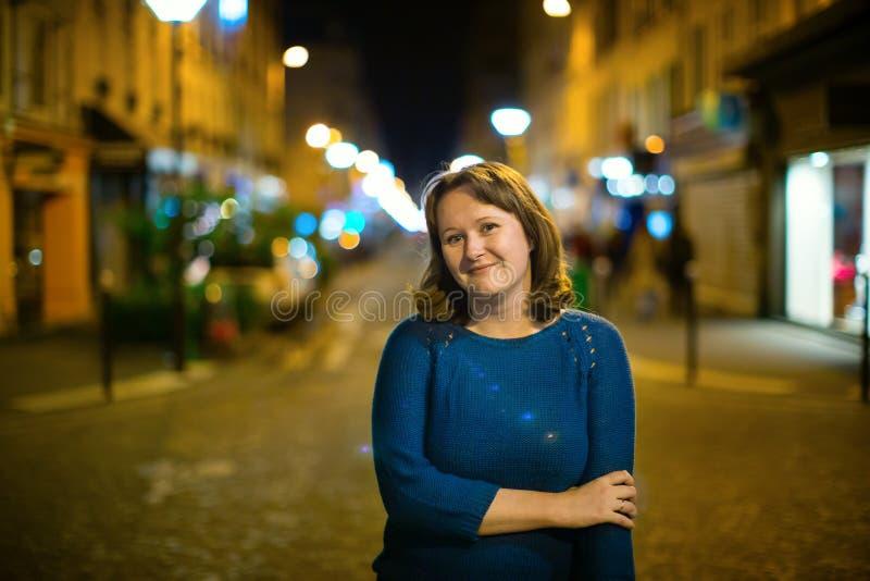 在一条街道上的微笑的女孩在晚上 库存图片