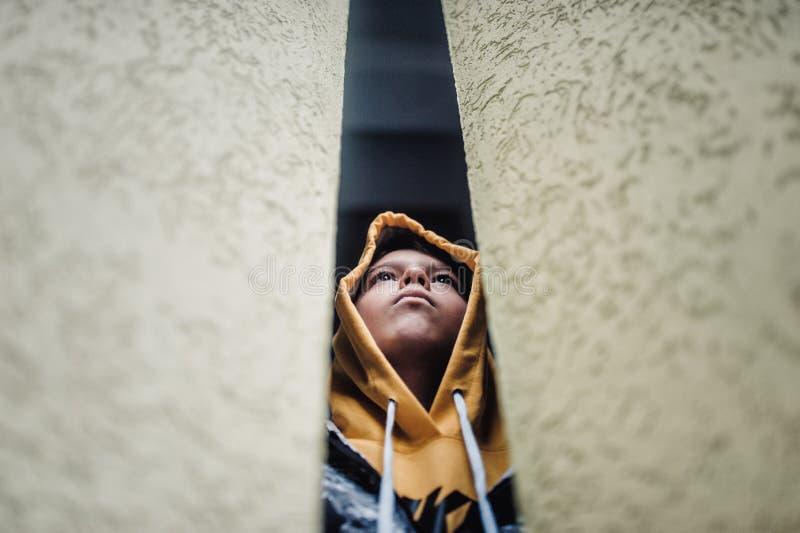 在一条街道上的青春期前的男孩在单独一座高层建筑物旁边的一个大城市 库存照片