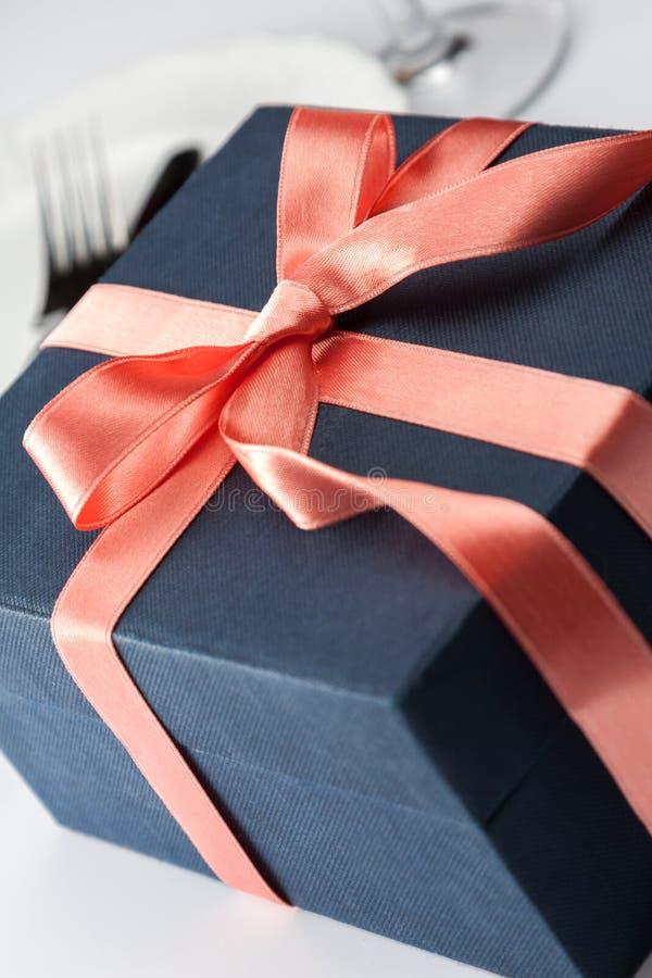 在一条装饰红色丝带的礼物盒 库存图片